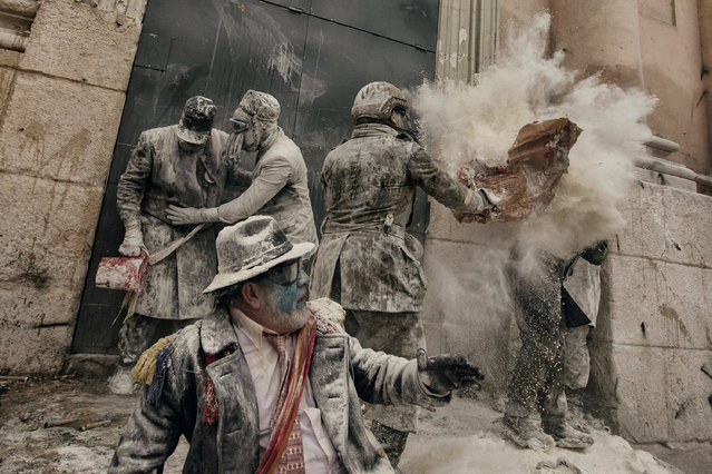 """On 28 December each year, the """"Floured War"""" takes place in Ibi in the province of Alicante, Spain. During the festival, the citizens are divided into two groups: the 'Enfarinat' (the floured) group simulates a coup d'etat and a second group tries to calm the rebellion. The teams play with flour, water, eggs and colored smoke bombs. The 200-year-old tradition is known as """"Els Enfarinats"""", marking the biblical Massacre of the Innocents by King Herod. (Photo by Antonio Gibotta/Reuters/Agenzia Controluce/Courtesy of World Press Photo Foundation)"""