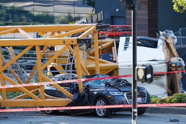 Emergency crews work at the scene of a construction crane collapse where several people were killed and others were injured Saturday, April 27, 2019, in the South Lake Union neighborhood of Seattle. The crane collapsed near the intersection of Mercer Street and Fairview Avenue pinning cars underneath it near Interstate 5. (Photo by Joe Nicholson/AP Photo)