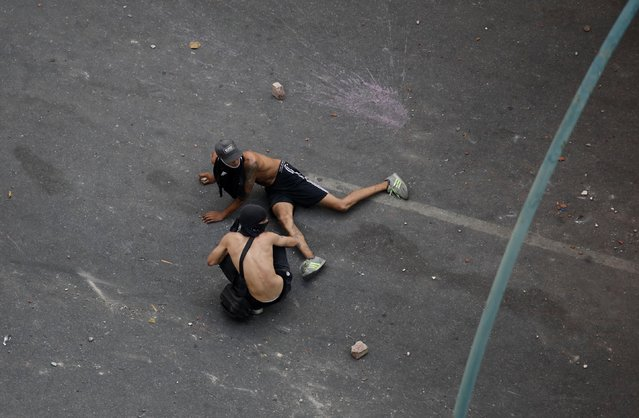 Demonstrators lay on the ground as they react to the sound of gunfire during clashes with security forces following a rally against the government of Venezuela's President Nicolas Maduro and to commemorate May Day in Caracas, May 1, 2019. (Photo by Adriana Loureiro/Reuters)