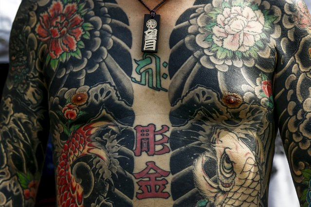 A man shows his traditional full body tattoo as he poses outside the Sensoji temple during the Sanja Matsuri festival in the Asakusa district of Tokyo May 17, 2015. (Photo by Thomas Peter/Reuters)
