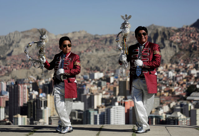 """Santos Poma and his grandson Ariel pose for a photo before a parade in honor of """"Senor del Gran Poder"""" (Lord of Great Power) in La Paz, Bolivia, June 6, 2019. (Photo by David Mercado/Reuters)"""