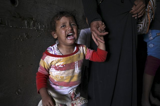 A girl cries next to her mother as they sit inside an underground water tunnel with other displaced Yemeni families, after they were forced to flee their home due to ongoing air-strikes carried out by the Saudi-led coalition in Sanaa May 2, 2015. (Photo by Mohamed al-Sayaghi/Reuters)