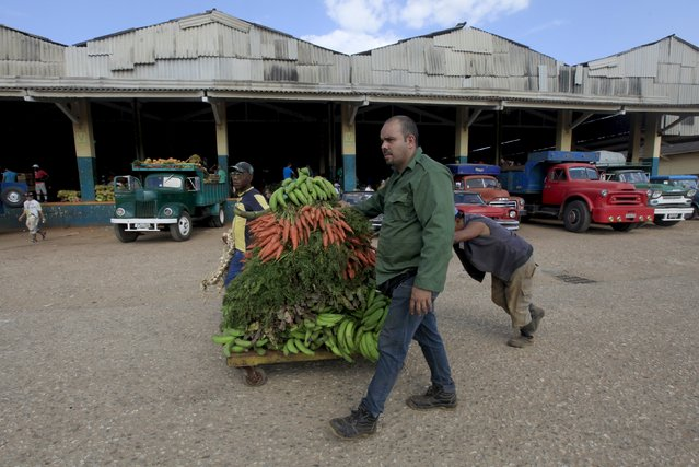 Men push a cart with vegetables and fruits at a wholesale market in Havana April 13, 2016. (Photo by Enrique de la Osa/Reuters)