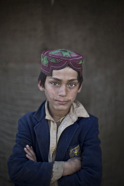 In this Sunday, January 26, 2014 photo, Afghan refugee boy, Ibraheem Rahees, 8, poses for a picture, in a slum on the outskirts of Islamabad, Pakistan. (Photo by Muhammed Muheisen/AP Photo)