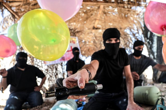 A Palestinian masked man prepares a balloon that will be attached to flammable materials and then flown toward Israel near the Israeli-Gazan border east Gaza city on June 27, 2019. (Photo by Dawoud Abo Al Kas/Quds Net News via ZUMA Press)