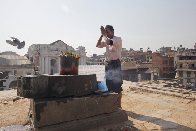 A Nepalese man offers prayers in front of a 'Siva Lingam', symbolic of Hindu god Shiva, as he worships at a temple that was completely destroyed in last year's earthquake at the Basantapur Durbar Square in Kathmandu, Nepal, Sunday, April 24, 2016. (Photo by Niranjan Shrestha/AP Photo)