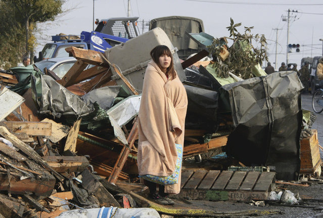A woman looks at the damage caused by a tsunami and an earthquake in Ishimaki City, Miyagi Prefecture, after the magnitude 8.9 earthquake struck the area March 13, 2011. (Photo by Yomiuri Shimbun/Reuters)