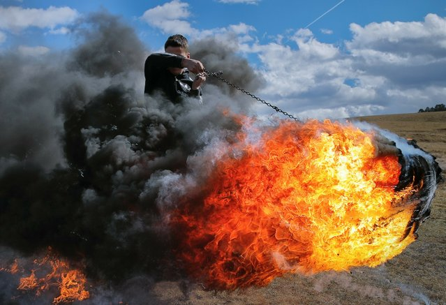 In this photo taken on Sunday, March 10, 2019, a young man spins a burning tire on a metal chain during a ritual marking the upcoming Clean Monday, the beginning of the Great Lent, 40 days ahead of Orthodox Easter, on the hills surrounding the village of Poplaca, in central Romania's Transylvania region. Romanian villagers burn piles of used tires then spin them in the Transylvanian hills in a ritual they believe will ward off evil spirits as they begin a period of 40 days of abstention, when Orthodox Christians cut out meat, fish, eggs, and dairy. (Photo by Vadim Ghirda/AP Photo)