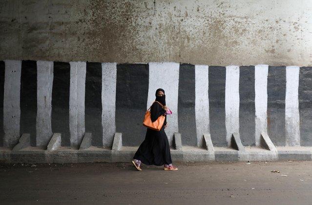 A veiled muslim woman walks across a road in the old quarters of Delhi, July 24, 2019. (Photo by Anushree Fadnavis/Reuters)