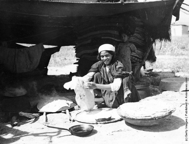 A Bedouin woman cooking flatbread outside her tent in Israel, circa 1950