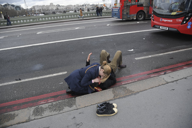 A woman assists an injured person after an incident on Westminster Bridge in London, Britain on Wednesday, March 22, 2017. (Photo by Toby Melville/Reuters)