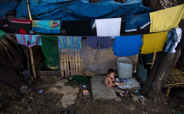 A child plays in front of his house in Hlaing Tharyar township on the outskirts of Yangon on June 26, 2019. (Photo by Sai Aung Main/AFP Photo)