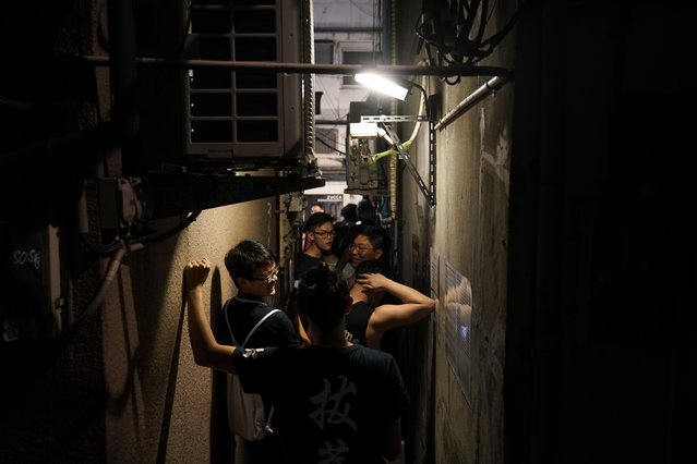 Tourists form a line along a narrow passageway outside a ramen restaurant at the Golden Gai in the Shinjuku district of Tokyo, July 26, 2019. (Photo by Jae C. Hong/AP Photo)