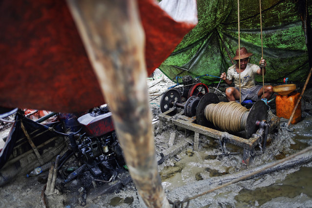 A man operates basic machinery to extract crude oil from a well in the Minhla township of the Magwe district October 27, 2013. (Photo by Damir Sagolj/Reuters)