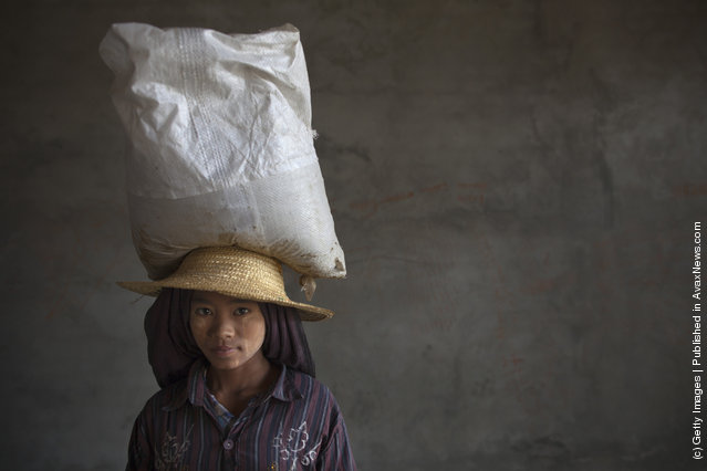 A young Burmese construction worker carries a large bag of cement at a hotel construction site
