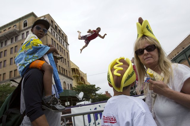A man leaps on a trampoline behind attendees before the annual Fourth of July 2015 Nathan's Famous Hot Dog Eating Contest in Brooklyn, New York July 4, 2015. (Photo by Andrew Kelly/Reuters)