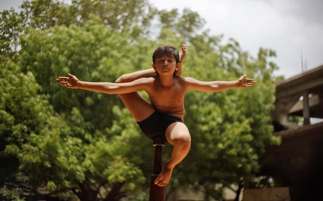 "An Indian boy practices ""Mallakhamb"", a traditional Indian gymnastic sport on a vertical wooden pole ahead of upcoming chariot festival of Lord Jagannath in Ahmadabad, India, Sunday, July 5, 2015. The festival will be celebrated on July 18, 2015. (Photo by Ajit Solanki/AP Photo)"