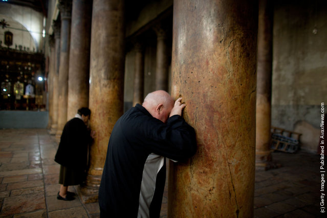 A man places his fingers into the crucifix-shaped holes in one of the ancient columns in the Church of the Nativity