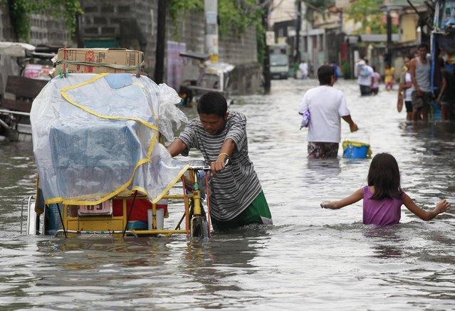 A man pushes his bicycle cart through waist-deep flooding caused by typhoon Linfa, locally named Egay, at Longos town in Malabon city, north of Manila July 6, 2015. (Photo by Romeo Ranoco/Reuters)