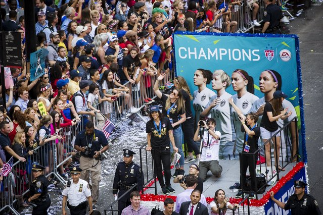 Fans of the U.S. women's soccer team cheer as members of the team ride a float during a ticker tape parade to celebrate their World Cup final win over Japan on Sunday, in New York, July 10, 2015. (Photo by Lucas Jackson/Reuters)