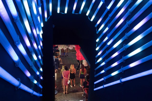 This photo taken on March 29, 2017 shows women standing in the entrance to a go go dance bar to entice customers to enter in Walking Street in Pattaya. (Photo by Roberto Schmidt/AFP Photo)