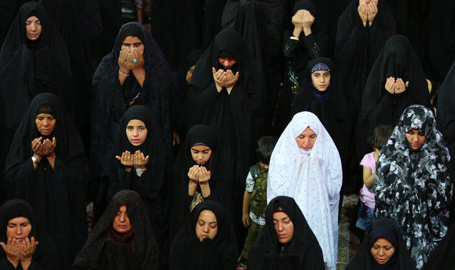 Muslim Shiite women pray at the shrine of Imam Ali, the son-in-law and cousin of the Prophet Muhammad and the first Imam of the Shiites, during the anniversary of his death, in the Shiite holy city of Najaf, 100 miles (160 kilometers) south of Baghdad, Iraq, early Friday, July 10, 2015. (Photo by Hadi Mizban/AP Photo)
