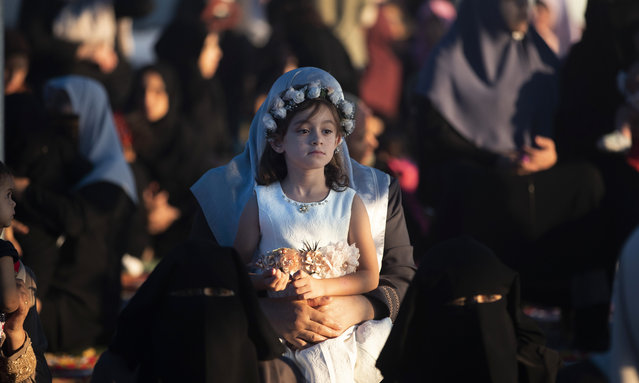 A Palestinian girl dressed up as she attends prayers to mark the first day of Eid al-Adha, in Gaza City, Sunday, August 11, 2019. During the Eid al-Adha, or Feast of Sacrifice, Muslims slaughter sheep or cattle to distribute portions of the meat to the poor. (Photo by Khalil Hamra/AP Photo)