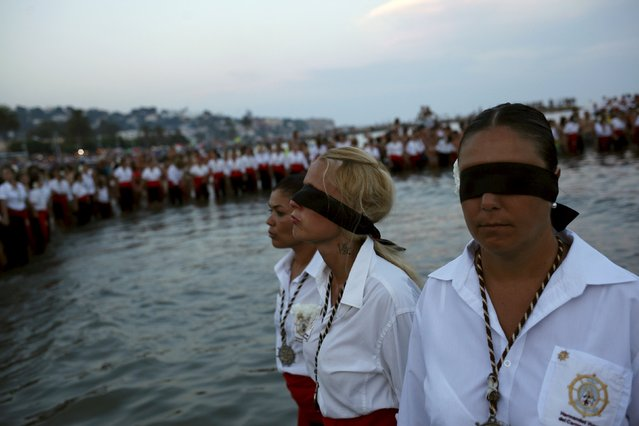 Women in traditional costumes wait for a statue of the El Carmen Virgin to be carried into the sea during a procession in Malaga July 16, 2015. (Photo by Jon Nazca/Reuters)