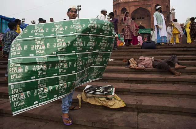 An Indian muslim man sells sheets to use as mat for Eid al-Fitr prayers outside the Jama Masjid mosque in New Delhi, India, Saturday, July 18, 2015. (Photo by Bernat Armangue/AP Photo)