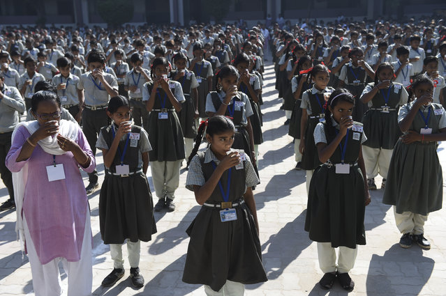 Students drink after participating in a jumping jack event to mark International Day of the Girl Child at Sarkhej Kelavni Mandal in Ahmedabad on October 11, 2019. (Photo by Sam Panthaky/AFP Photo)