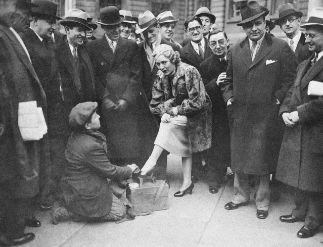 """It isn't often that celebrities, visiting the City Hall in New York City, pause to get a shine from the roving bootblacks in City Hall Park. But Mary Pickford did, when she visited Mayor F.H. LaGuardia in New York on January 31, 1934, and it was a big moment for Joe """"Fat"""" Barbera. Joe is at his job while bystanders look on. (Photo by AP Photo)"""