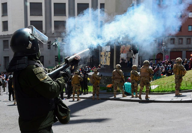 A riot policeman shoots tear gas at supporters of former Bolivian President Evo Morales during the funeral procession of eight people killed when security forces lifted a siege on a fuel plant, in La Paz, the November 21, 2019. (Photo by Aizar Raldes/AFP Photo)