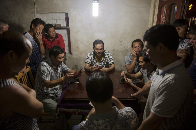 People play cards as others watch in a cafe on Shengshan island, China July 25, 2015. (Photo by Damir Sagolj/Reuters)
