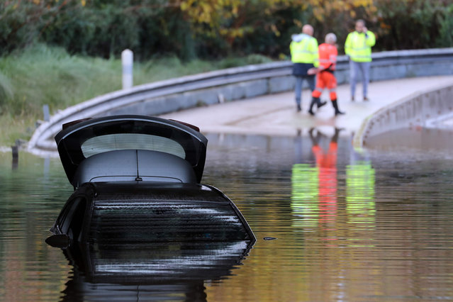 Rescuers walk by a car partially submerged in the water on a flooded road of Mandelieu-la-Napoule, on December 2, 2019, southern France, following fresh torrential rains over the French Riviera. (Photo by Valery Hache/AFP Photo)