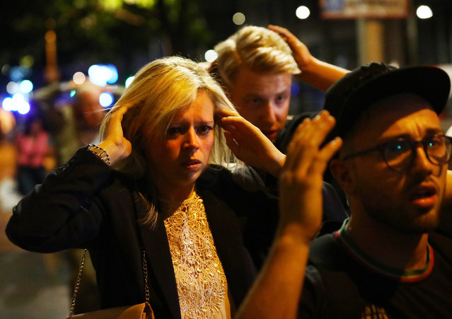 People leave the area with their hands up after an incident near London Bridge in London on June 4, 2017 following a terrorist attack on London Bridge and Borough Market. (Photo by Neil Hall/Reuters)