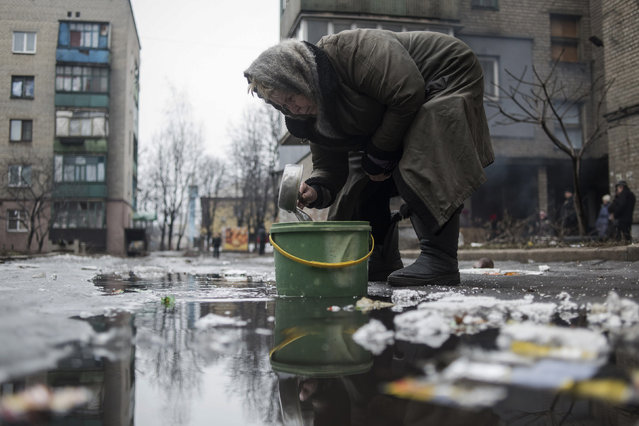An elderly woman collects water from a puddle in Debaltseve, February 3, 2015. Five Ukrainian soldiers have been killed and 27 wounded in fighting with pro-Russian separatists in Ukraine's eastern regions in the past 24 hours, Kiev military spokesman Andriy Lysenko said on Tuesday. Ukrainian military say fighting has been particularly intense around the town of Debaltseve, a major rail and road junction northeast of the city of Donetsk, which government troops are still holding. (Photo by Sergey Polezhaka/Reuters)