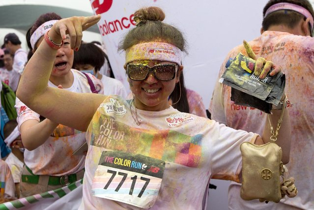 A woman covered by color powder gestures to journalists during a five-kilometer color run event in Beijing, China Saturday, June 21, 2014. (Photo by Andy Wong/AP Photo)