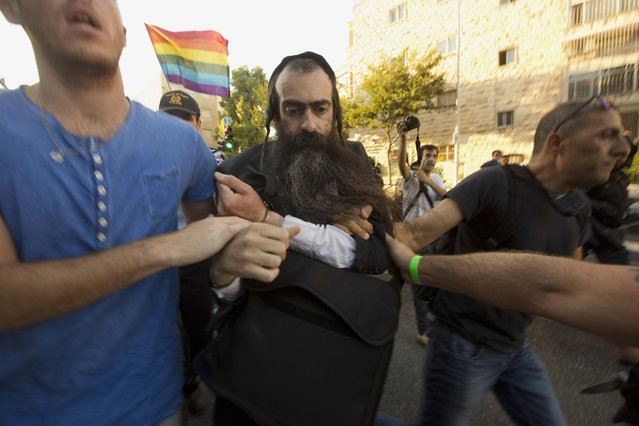 Ultra Orthodox Jew Yishai Schlissel is detained by plain-clothes police officers after he stabbed people during a gay pride parade in Jerusalem on Thursday, July 30, 2015. Schlisse was recently released from prison after serving a term for stabbing several people at a gay pride parade in 2005, a police spokeswoman said. (Photo by Sebastian Scheiner/AP Photo)
