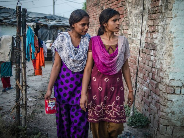 Kajal Gautam (16) with her close friend and cousin Sarita Gautam (17) walk in the evening to a toilet in an open defecation area of the village, Nihura Basti, Kanpur. (Photo by Poulomi Basu/WaterAid)