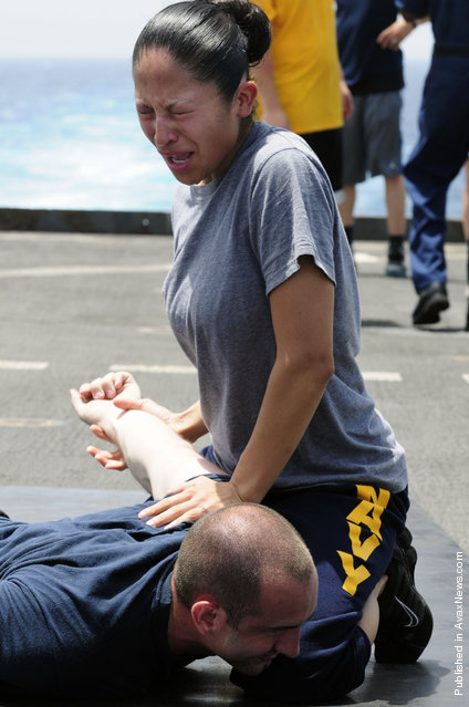 Culinary Specialist 2nd Class Jaqueline Rodriguez subdues a simulated suspect after being sprayed with oleoresin capsicum (OC) spray during security training aboard the amphibious dock landing ship USS Comstock (LSD 45)