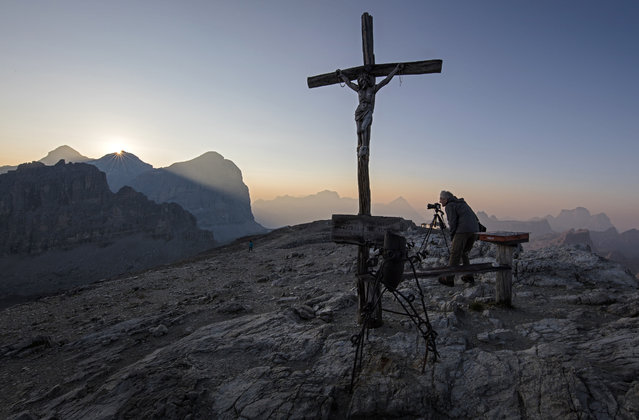 A photographer takes pictures as the sun rises over the Dolomite Mountains near Cortina d' Ampezzo in northern Italy July 17, 2015. (Photo by Bob Strong/Reuters)