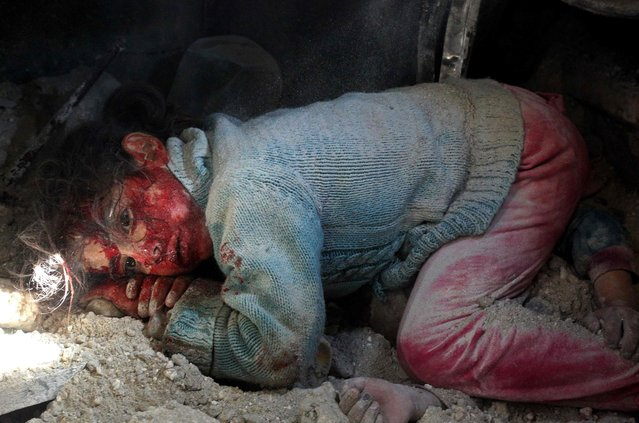 A wounded Syrian girl awaits rescue from under the rubble next to the body of her sister (hands seen-R) who did not survive regime bombardment in Khan Sheikhun in the southern countryside of the rebel-held Idlib province, on February 26, 2019. Regime bombardment near Khan Sheikhun, in Idlib province, killed two civilians on Tuesday, raising the civilian death toll to 42 since February 9, the Britain-based Syrian Observatory for Human Rights said. (Photo by Anas Al-Dyab/AFP Photo)