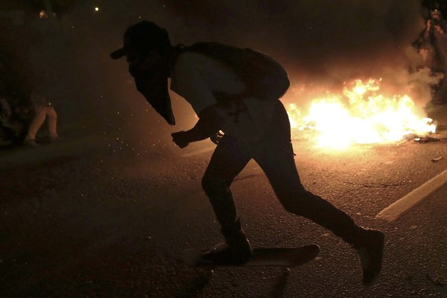 A demonstrator skates in front of a burning barricade in the Marginal Pinheiros area during a protest against the 2014 World Cup, in Sao Paulo June 19, 2014. (Photo by Nacho Doce/Reuters)