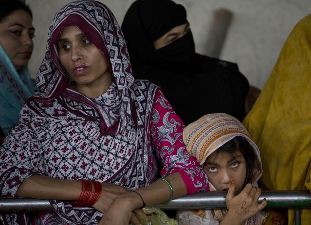 People wait in a queue for food donations distributed at a local shrine in Islamabad, Pakistan, Thursday, July 23, 2015. (Photo by B. K. Bangash/AP Photo)