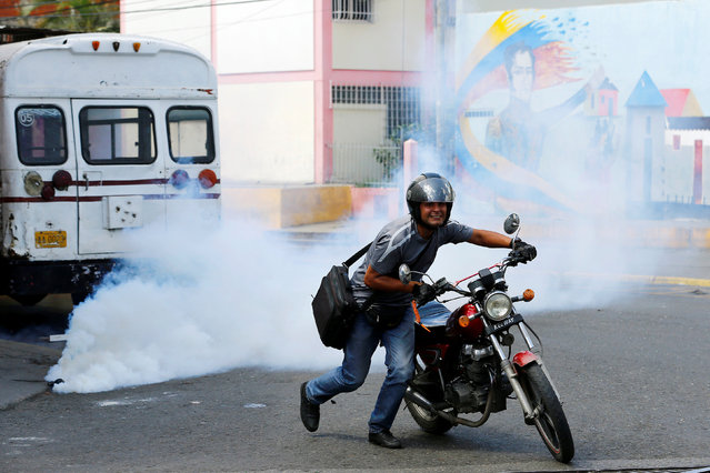 A local runs away from tear gas released by riot policemen after a protest over food shortage and against Venezuela's government in Caracas, Venezuela, June 10, 2016. (Photo by Ivan Alvarado/Reuters)