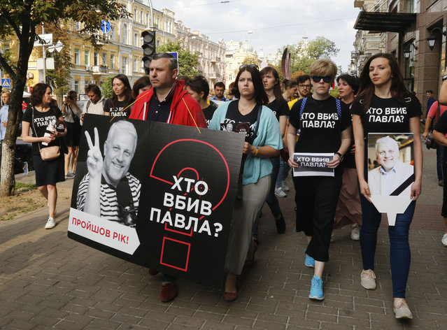 """Activists and journalists march to pay tribute to murdered journalist Pavel Sheremet, wearing T-shirts that read """"Who killed Pavel?"""", in Kiev, Ukraine, Thursday, July 20, 2017. Sheremet, 44, was killed in Kiev in a car explosion last year. Despite promises from President Petro Poroshenko to solve the case, no progress is visible a year after the killing and Ukrainian journalists say the inaction leaves them feeling increasingly imperiled. (Photo by Efrem Lukatsky/AP Photo)"""