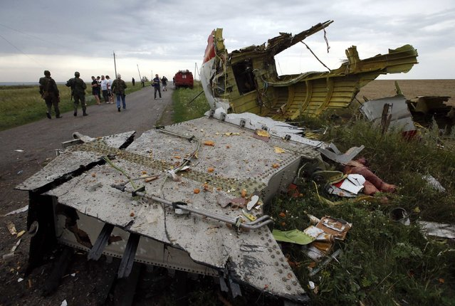 People stand near part of the wreckage of a Malaysia Airlines Boeing 777 plane after it crashed near the settlement of Grabovo in the Donetsk region, July 17, 2014. The Malaysian airliner Flight MH-17 was brought down over eastern Ukraine on Thursday, killing all 295 people aboard and sharply raising stakes in a conflict between Kiev and pro-Moscow rebels in which Russia and the West back opposing sides. (Photo by Maxim Zmeyev/Reuters)