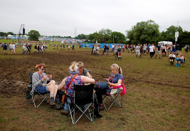 Revellers sit around a table in a field near the Pyramid stage during the Glastonbury Festival at Worthy Farm in Somerset, Britain June 23, 2016. (Photo by Stoyan Nenov/Reuters)