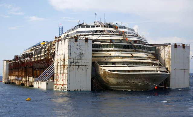 The Costa Concordia cruise liner is seen during its refloat operation at Giglio harbour July 22, 2014. The massive hulk of the Costa Concordia is nearly ready to be towed away from the Italian island where it struck a rock and capsized two-and-a-half years ago, killing 32 people, officials said on Sunday. The 114,500-tonne Concordia has been slowly lifted from the sea floor since Monday, when salvagers began pumping air into 30 large metal boxes, or sponsons, attached around the hull. (Photo by Max Rossi/Reuters)