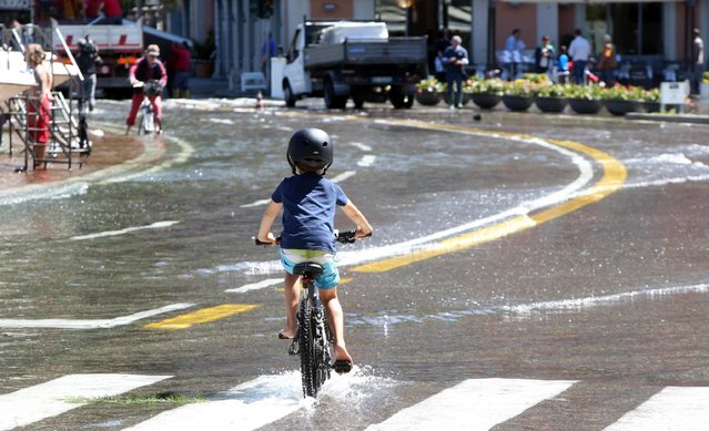 A child rides his bike through flood waters as Lake Como overflows at Cavour square in Como, Italy, 17 June 2016. (Photo by Matteo Bazzi/EPA)